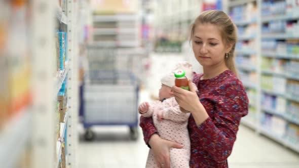 Thumbnail for Frau Wahl Kinder Essen mit Little Baby Kind Mädchen auf Händen während Supermarkt Shopping