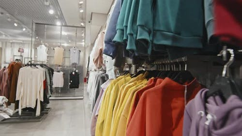 Bright Color Clothes Hanging On Racks In Store