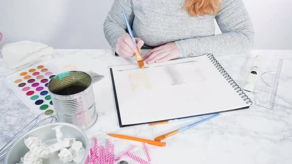 Thumbnail for Baker is drawing the design of a birthday cake with watercolors.