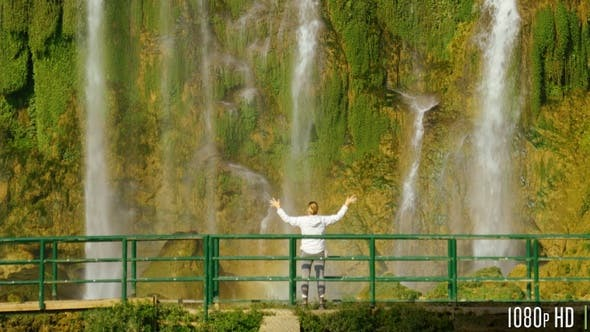 Thumbnail for Woman Standing by Waterfall with Her Raised Hands