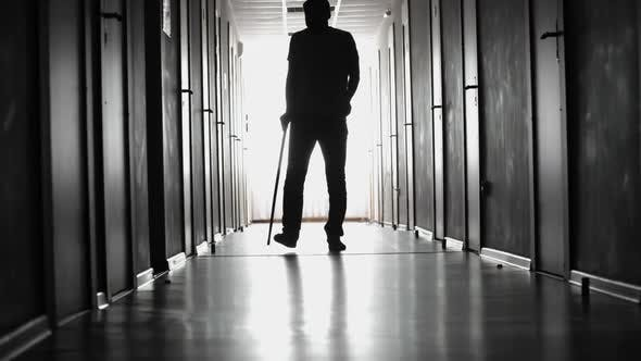 Thumbnail for Limping Man Walking along Hospital Corridor
