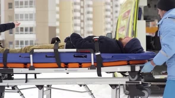 Thumbnail for Team of Paramedics Lifting Stretcher into Ambulance