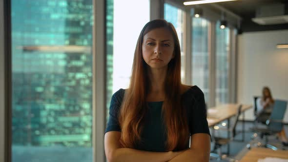 Thumbnail for Portrait of Young Successful Redhair Businesswoman Standing in Office Hall Looking at Camera