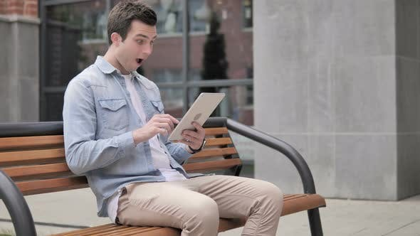 Thumbnail for Casual Young Man Sitting Outdoor and Cheering Success on Tablet