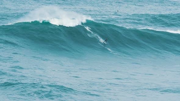 Thumbnail for Surfer Rolls on Huge Wave on a Surf at Competitions Drone Shoots Process, Slow Motion