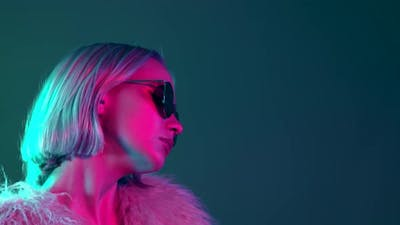 Glamorous Hipster Teenager in Sunglasses and Furry Coat Dancing To Music with Sunglasses. Portrait