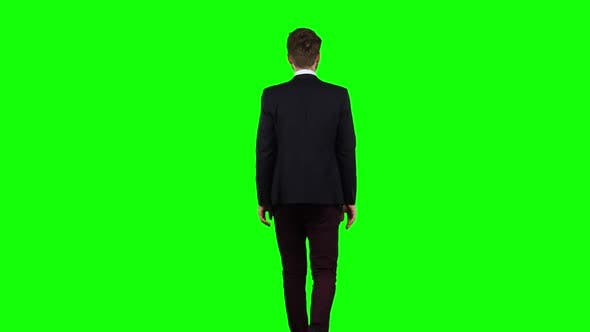 Thumbnail for Man Is Going To a Meeting and Waving Greetings. Green Screen. Back View
