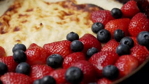 Fried Curd Pie in a Frying Pan with Strawberries and Blueberries on a Wooden Table