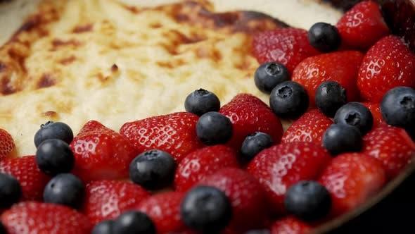 Gebratener Quarkkuchen in einer Bratpfanne mit Erdbeeren und Blaubeeren auf einem Holztisch