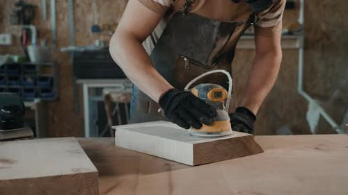 The Carpenter Works with the Electric Polisher on the Wood. Top View Man Craftman with Grinder