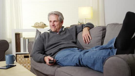 Elderly man watching tv on couch
