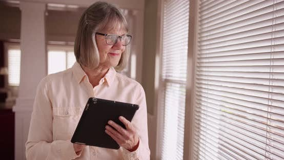 Gentle mature lady using wireless pad device by window in living room