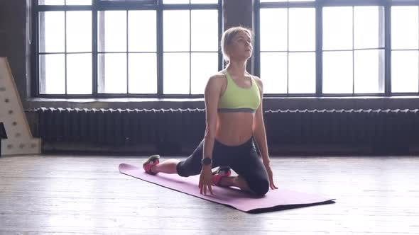 A Young Blonde Woman Is Doing Sports Sitting On A Mattress Stretching In A Fitness Studio