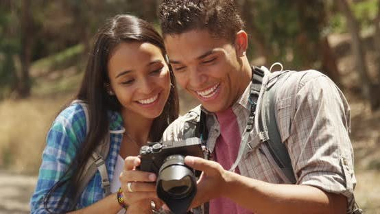 Young Mexican couple looking at pictures on camera