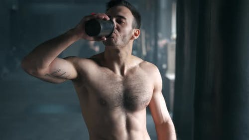 Attraktiver athletischer, gerissenloser junger Mann, der Protein-Shake aus Shaker im Fitnessstudio trinkt und anschaut