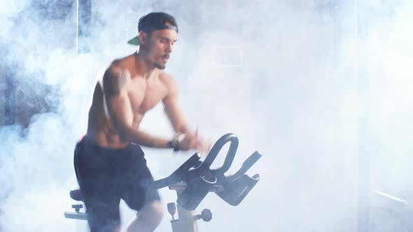 Thumbnail for Shirtless Athletic Man Training on Cycling Machine in Gym