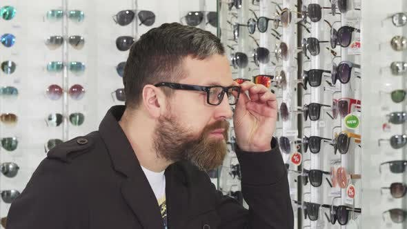 Thumbnail for Bearded Man Trying on Glasses at the Eyewear Store