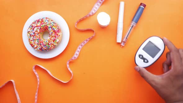 Diabetic Measurement Tools Insulin and Donuts on Orange Background