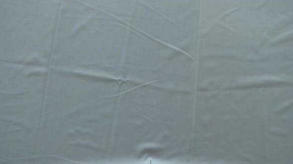Thumbnail for Tailor Cutting A Grey Cloth On A Table