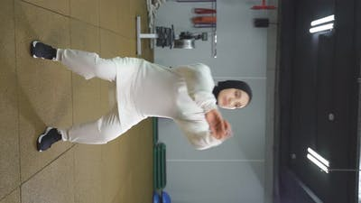 Arab Woman in a White Hijab Works Out in the Gym a Muslim Woman Squats in the Indoor Gym