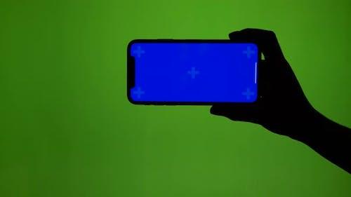 Mädchenhafte Hand hält horizontal Smartphone auf grünem Bildschirm