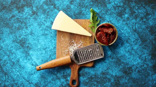 Thumbnail for Grated Parmesan Cheese and Metal Classic Grater Placed on Wooden Cutting Board