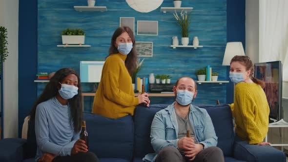 Freunde mit Schutzmaske verbringen Zeit im Wohnzimmer mit Online-Meeting