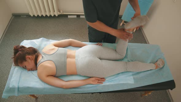 Thumbnail for Woman Having an Osteopath Treatment - the Doctor Warming Up Her Knee and the Leg - Pushing It To the
