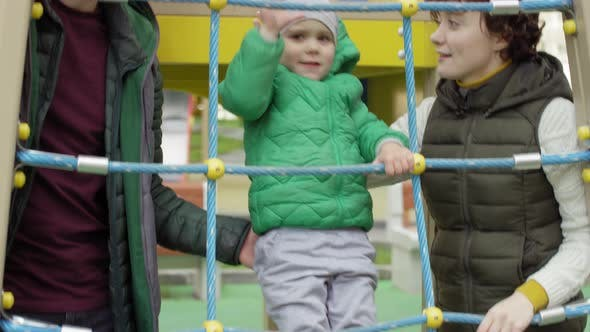 Thumbnail for Boy Climbing at Playground and Parents Guarding Him