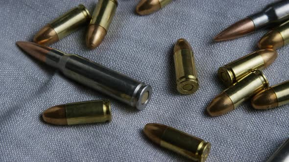 Thumbnail for Cinematic rotating shot of bullets on a fabric surface