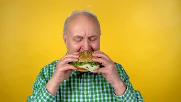 Thumbnail for Cheerful Elderly Man Enjoying Burger