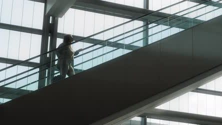 Woman with suitcase going up the escalator, slow motion, 4K