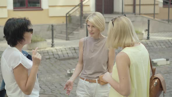 Thumbnail for Slim Mid-adult Woman Talking with Friends on European City Street. Portrait of Three Female