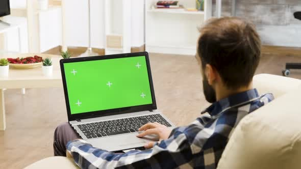 Thumbnail for Man Sitting on the Sofa with a Green Screen Laptop in His Lap