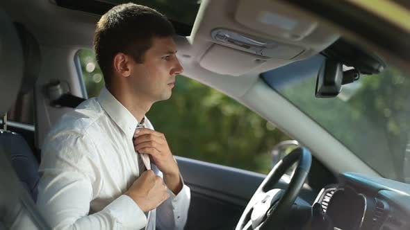 Thumbnail for Successful Businessman Fixing Tie in Car