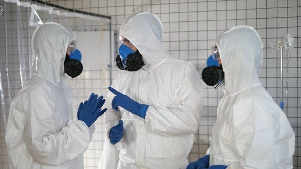 Thumbnail for Group of doctors in protective suits having serious discussion.