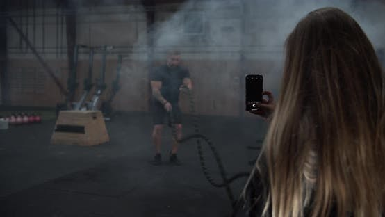 Thumbnail for Supportive Girlfriend Taking Photos of Fit Boyfriend While Doing the Battle Rope