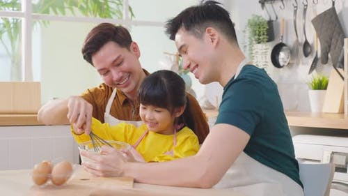 Asian attractive LGBTQ gay family feel enjoyment and teach girl kid making yeast dough.