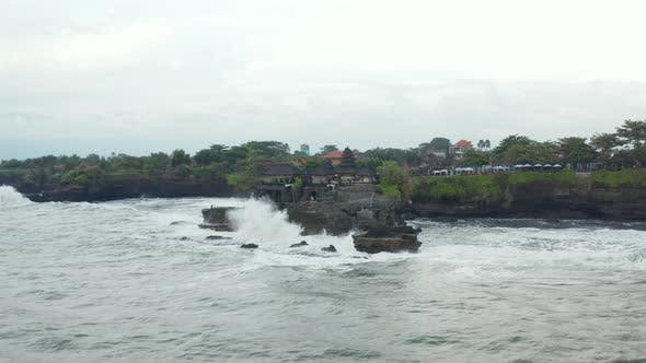 Low Aerial Shot Approaching Famous Tanah Lot Temple Tourist Destination in Bali Indonesia