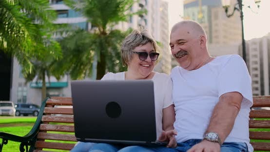 Thumbnail for Happy Senior Couple Sitting on a Bench in the Summer in a Modern City with a Laptop