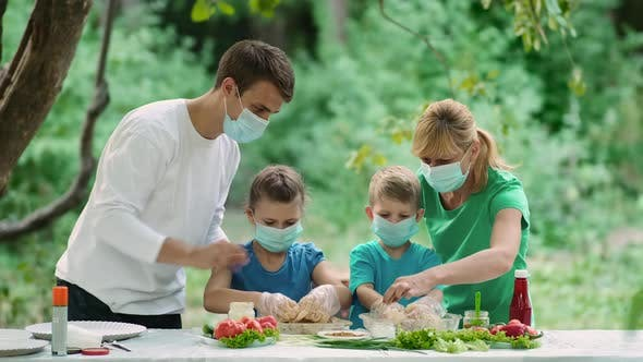 Dad and mom teach children how to cook grilled meat, Family in medical masks on a picnic in nature
