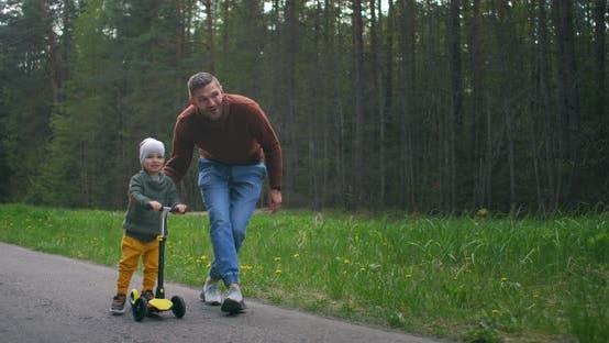 In Zeitlupe lehrt ein junger glücklicher Vater seinen 2-jährigen Sohn, einen Roller in einem Park auf einem