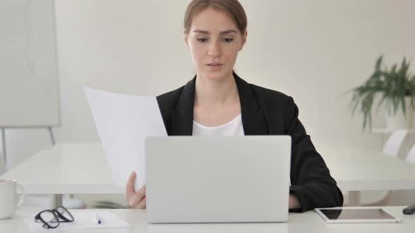 Businesswoman Working on Documents and Laptop