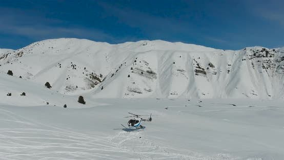 Thumbnail for Aerial view White Helicopter landing in the snow mountains