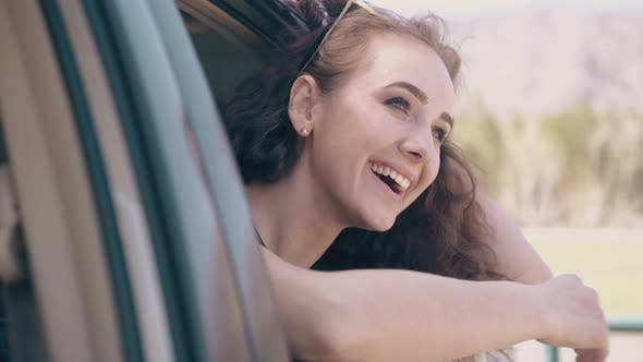Thumbnail for Girl with Loose Hair Laughs in Car Against Blurred Field