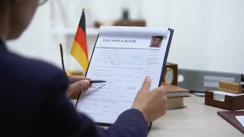 Embassy Employee Approving Visa Application, German Flag on Table, Authority