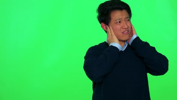Thumbnail for A Young Asian Man Covers His Ears and Grimaces Against a Loud Sound - Green Screen Studio