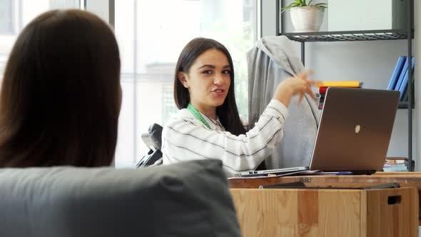 Thumbnail for Junge Attraktive weibliche Designerin Diskutieren T-Shirt mit Ihrem Kollegen