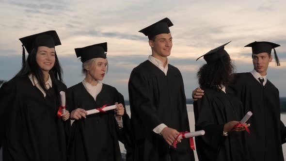 Thumbnail for Group of Happy Graduates Walking To Graduation Ceremony in the Evening