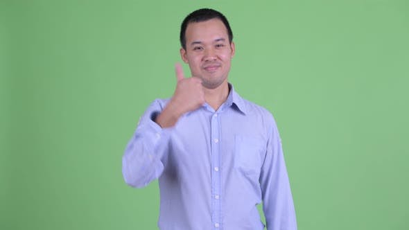 Thumbnail for Studio Shot of Happy Asian Businessman Giving Thumbs Up